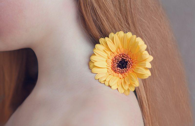 Oberkörper und Haare einer Person mit einer gelben Blume