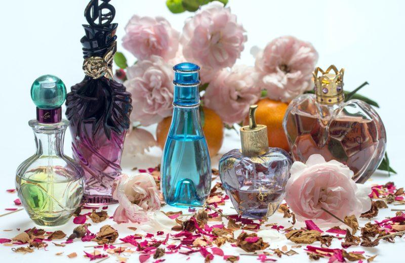 Viele farben- und formenfrohe Parfums stehen vor und auf einem Blütenmeer - ist hier das Sommerparfum 2017 dabei?