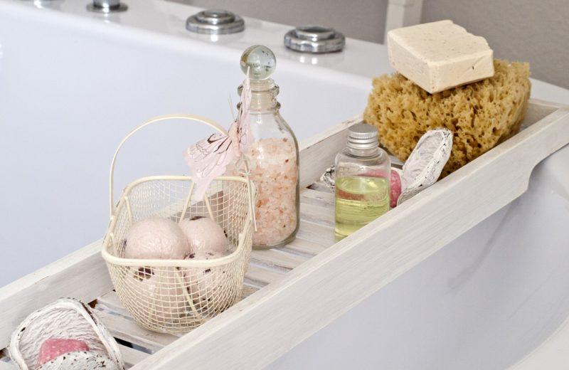 Auf einer Ablage über der Badewanne stehen verschiedene Arten von Badezusatz