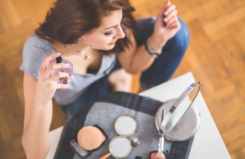 Eine Frau sitzt an einem kleinen Schminktisch und sprüht sich Parfum auf