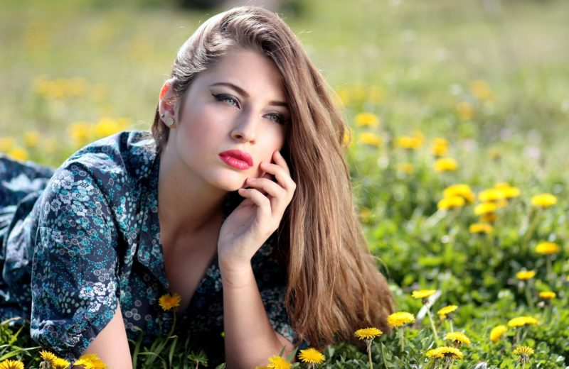 Frau mit geschminkten Augen liegt im Gras