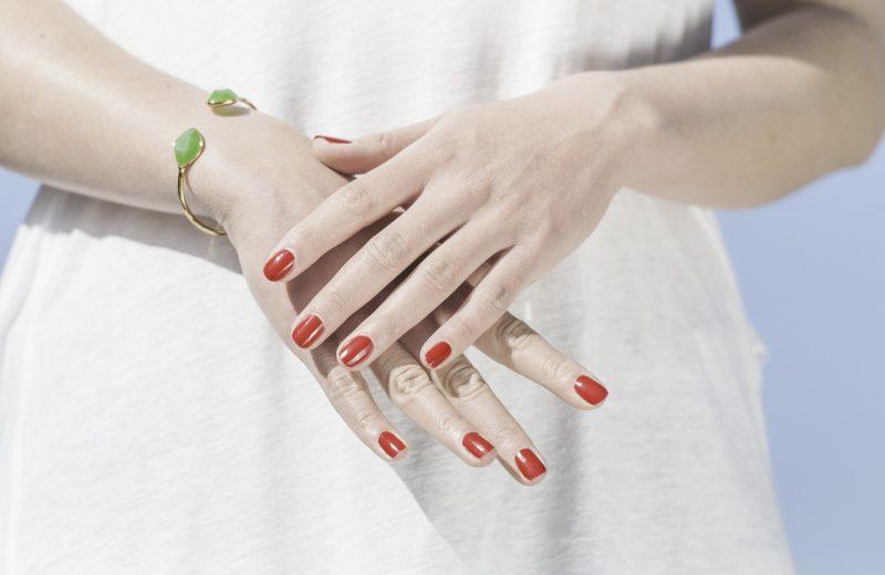 Eine Frau im weißen Kleid mit übereinandergelegten Händen samt rot lackierter Fingernägel