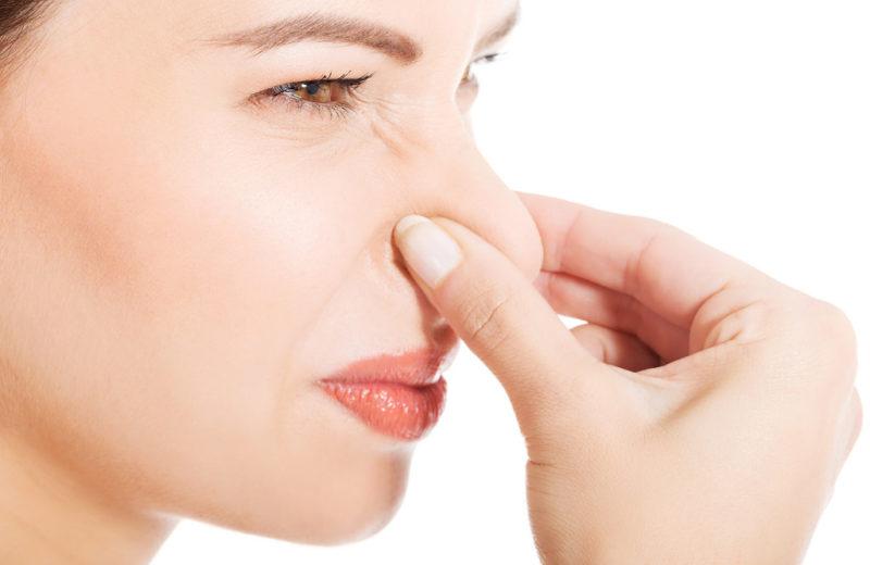 Eine Frau hält sich wegen eines strengen Geruchs die Nase zu