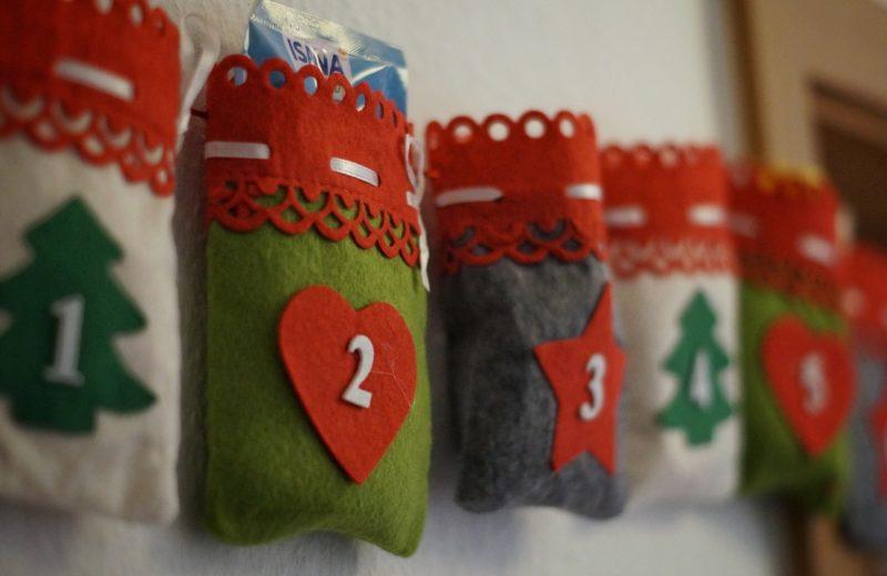 An einer Wand aufgehängt ist ein Adventskalender, der aus vielen kleinen Stoffsäckchen in Rot, Grün und Beige besteht
