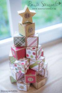 Ein Adventskalender aus bunten kleinen Schachteln, die zu einer Pyramide aufgestapelt sind