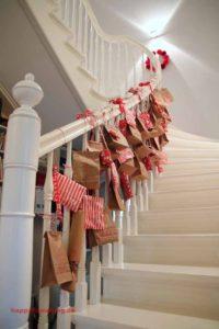 Ein Adventskalender aus braunen, verzierten Brottüten hängt an einem Treppengeländer