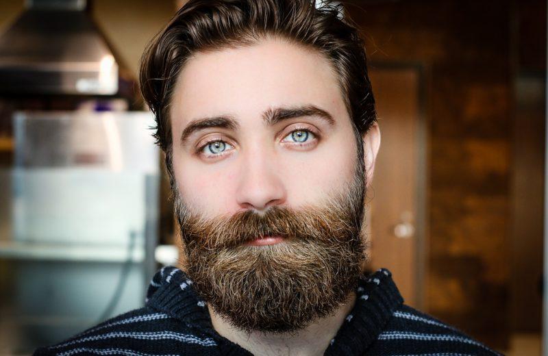Ein Mann mit Vollbart und strahlend blauen Augen schaut nachdenklich in die Kamera