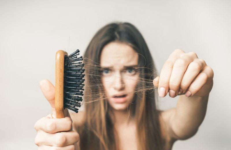 Eine Frau zieht Haare aus ihrer Haarbürste