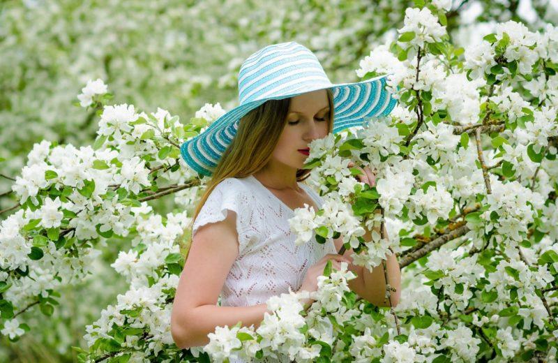 Eine Frau in einem weißen Kleid und einem großen Sonnenhut riecht an den weißen Blüten eines Baumes.
