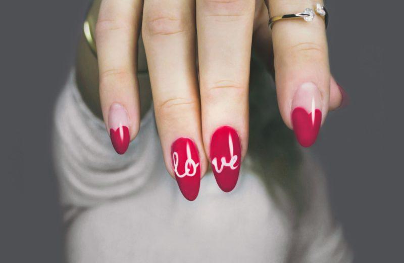 """Eine Frau hält ihre Nägel in die Kamera, die mit rotem Nagellack und einer weißen Schrift """"Love"""" manikürt wurden."""