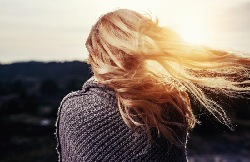 Eine Frau steht mit dem Rücken zur Kamera und betrachtet einen Sonnenuntergang. Ihre langen, blonden Haare wehen im Wind