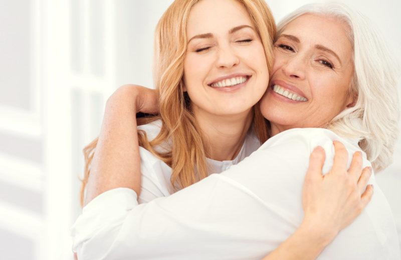 Eine junge blonde Frau umarmt eine ältere Frau mit hellgrauen Haaren. Beide sehen gepflegt aus, tragen weiße Kleidung und lächeln.