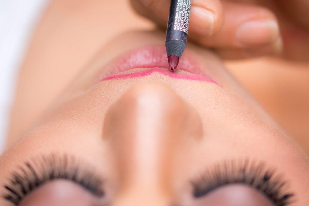 Einer Frau wird mit einem Lipliner die Lippenkontur nachgezogen.