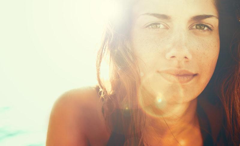 Ob durch die Sonne oder Selbstbräuner - eine junge Frau mit schön gebräunter Haut lächelt im Sonnenschein in die Kamera