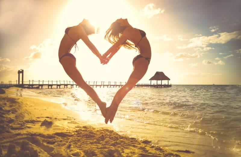 Zwei Frauen springen Händchen haltend Rücken an Rücken am Strand in die Höhe, sodass sie ein Herz formen. Hinter ihnen geht die Sonne unter.