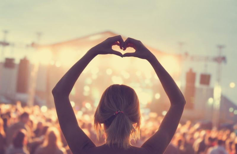 Eine Frau ist von hinten zu sehen, sie hat die Arme über dem Kopf und formt mit den Händen ein Herz. Im Hintergrund sieht man eine Festival-Kulisse mit vielen Menschen und einer Bühne.