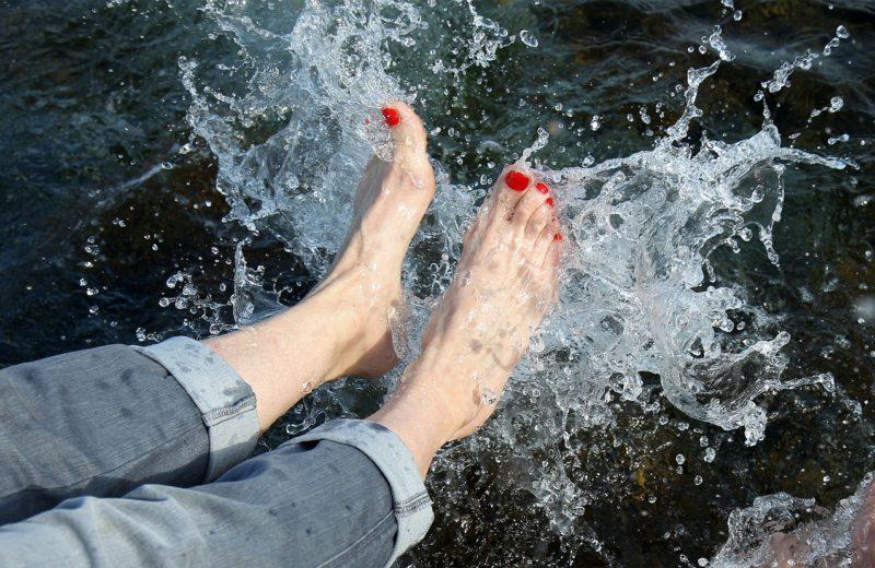 Eine Frau mit hochgekrempelten Jeans und rot lackierten Fußnägeln sitzt am Wasser und planscht mit den Füßen, dass es nur so spritzt.