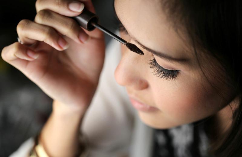 Eine Frau mit dunklen Haaren tuscht sich ihre Wimpern