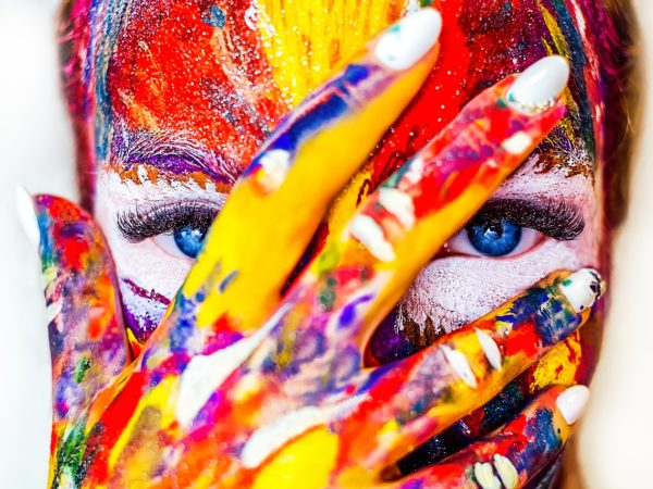 Ein Frauengesicht ist über und über mit bunter Farbe beschmiert. Die Frau hält eine Hand vors Gesicht, nur ihre Augen sind ohne Farbe.