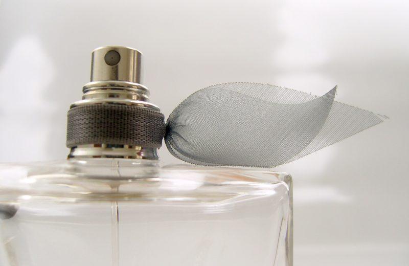 Nahaufnahme eines durchsichtigen Parfum-Flakons in klassischer Form, um dessen Zerstäuber ein schwarzes Band aus Tüll gebunden ist.