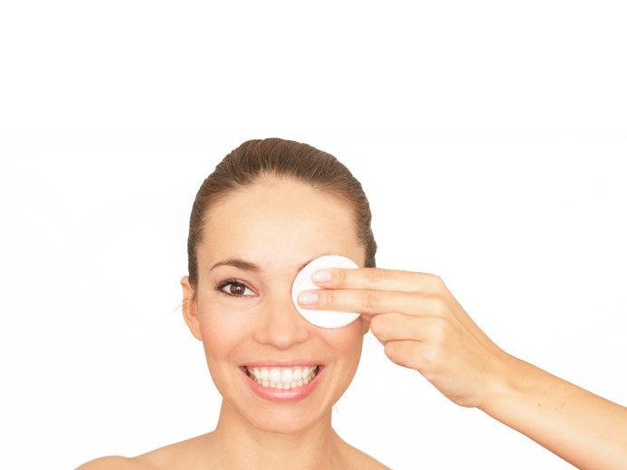 Eine Frau wischt sich mit einem Wattepad über das Auge.