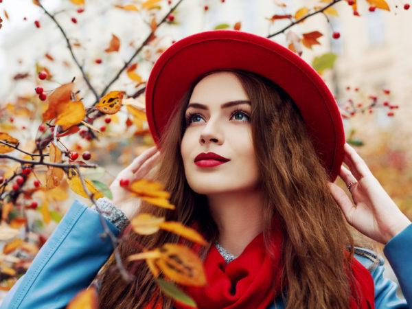 Eine Frau mit langen braunen Haaren steht vor einem Busch mit Herbstlaub. Sie trägt eine blaue Jacke, einen roten Schal und Hut, den sie mit beiden Händen festhält. Ihre Lippen sind rot, was einer der Make-Up Trends 2019 ist.