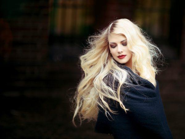 Eine Frau mit langen blondierten Haaren schaut über ihre Schulter, während ihre Haare wehen.