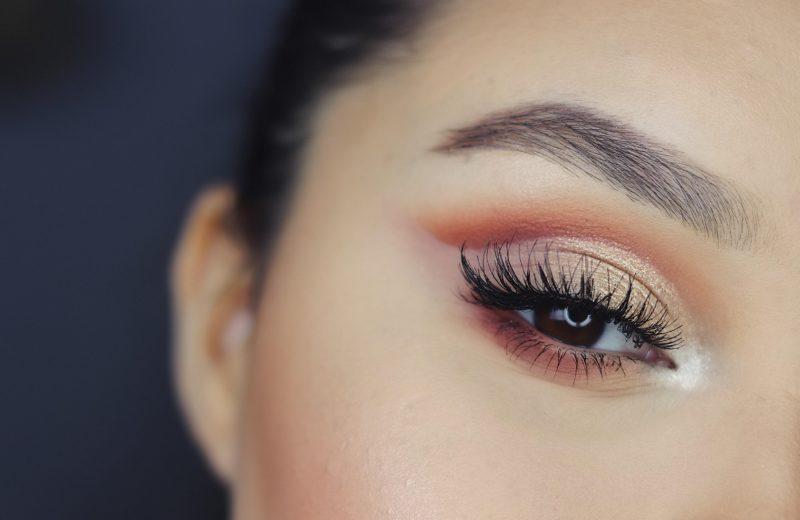 Man sieht ein Stück eines Frauengesichtes. Es ist um die Augen sehr schön in Gold- und Rotbraun-Tönen geschminkt und hat getuschte Wimpern.