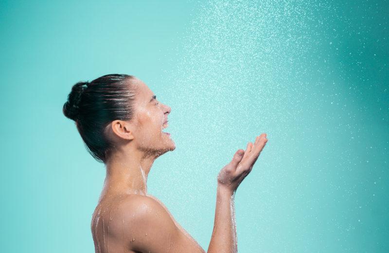 Eine Frau steht seitlich vor einem türkisfarbenen Hintergrund. Von oben fällt Wasser wie aus einer Dusche. Sie fängt es mit beiden Händen auf und lacht.