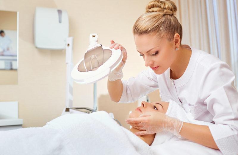 Eine Dermatologin oder Kosmetikerin im weißen Kittel macht bei einer liegenden Frau eine Hautanalyse. Dafür hat sie verschiedene Utensilien (z.B. eine Lupe) zur Hand.