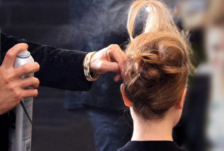 Eine Frau bekommt eine Hochsteckfrisur gemacht. Dabei verwendet der Frisierende Haarstyling Produkte wie Haarspray.