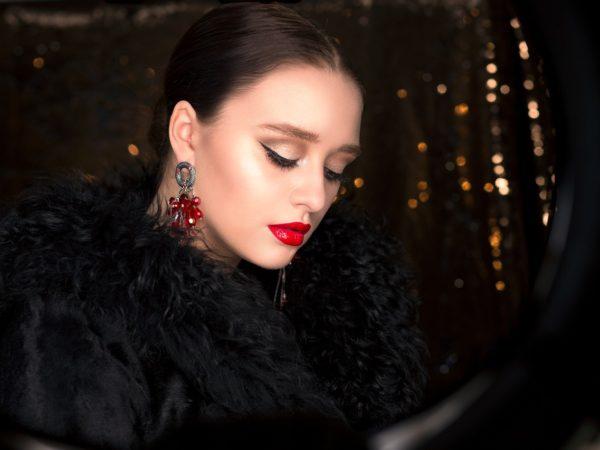 Eine Frau mit dunklen Haaren und dunklem Mantel an steht vor einem Glitzernden Hintergrund. Sie ist mit roten Lippen und Highlighter geschminkt.