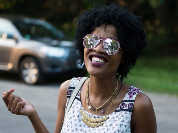 Eine farbige Frau im sommerlichen Outfit und Sonnenbrille auf, zeigt bei einem breiten Lachen ihre schönen Zähne.