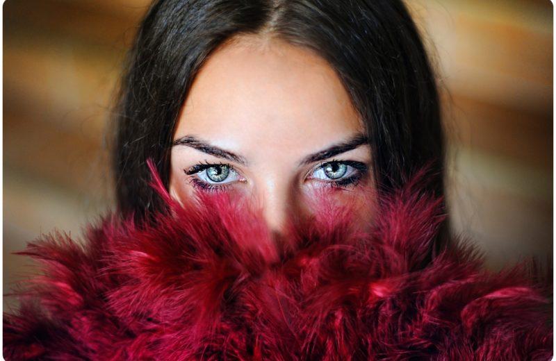 Eine Frau die ihre geschminkten Augen zeigt.